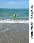 Small photo of Two children swim on a crocodile - air bed in the sea , with wave in the foreground