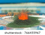 Small photo of chemical reaction of ammonium dichromate if to set fire to it on the foil