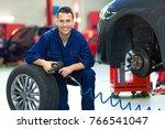 mechanic working on car in auto ... | Shutterstock . vector #766541047