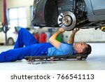 mechanic working on car in auto ... | Shutterstock . vector #766541113