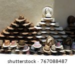 A Stack Of Straw Hats Of...