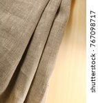 Small photo of Linen unpainted fabric with folds on the background of wood