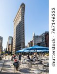 Small photo of NEW YORK, USA - OCT 5, 2017: people enjoy sitting at broadwayon public chairs with free wlan and looking to the spectacular facade of Flatiron building.