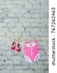 Small photo of Children's pink body, bib and red shoes, dry on a rope against a white brick wall.