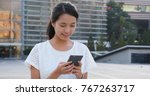 young woman using cellphone  | Shutterstock . vector #767263717