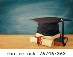 Small photo of Image of graduation black hat over old books next to graduation on wooden desk. Education and back to school concept