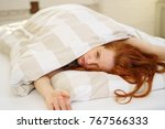 Small photo of Sleepy sultry young redhead woman peering out from under her duvet in bed loathe to get up