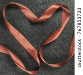 Small photo of The rope is laid out in the shape of heart on black background, top view