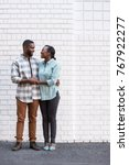 Small photo of Affectionate young African couple smiling while standing together in front of a brick wall in the city
