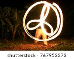 Small photo of A fire dander spins fire on balls with chains (poi) on a beach.