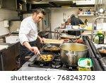 chef in a restaurant kitchen... | Shutterstock . vector #768243703