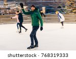 Small photo of Happy male waves with hand as notices his friend on skating ring, have desire to skate together, rejoices meeting, has good time and mood, entertains himself. People and winter activities