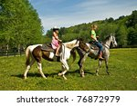 A young girl getting a horseback riding lesson. - stock photo