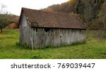 Small photo of Partially broken old country barn with missing boards and small roof tiles surrounded with high uncut grass, plants and large trees