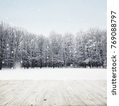 wooden table over winter snow... | Shutterstock . vector #769088797