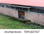 Small photo of Brick building with small old wooden doors, multiple small windows, metal roof, stone entrance covered with moss and uncut grass in front