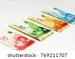 Small photo of Israeli money - diagonal view of a stack of Israeli money bills (banknotes) of 20, 50,100 and 200 shekel isolated on white. New Israeli Shekel series C. Selective focus