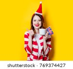 Small photo of Portrait of young redhead woman in Santa Claus hat and striped shirt with Great Britain flag and cup of tea on yellow background. Christmas time