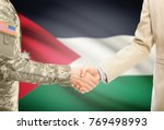 Small photo of American soldier in uniform and civil man in suit shaking hands with adequate national flag on background - Jordan
