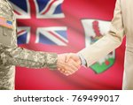 Small photo of American soldier in uniform and civil man in suit shaking hands with adequate national flag on background - Bermuda