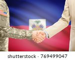 Small photo of American soldier in uniform and civil man in suit shaking hands with adequate national flag on background - Haiti