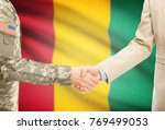 Small photo of American soldier in uniform and civil man in suit shaking hands with adequate national flag on background - Guinea