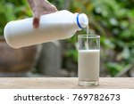 hand on pour milk to glass | Shutterstock . vector #769782673