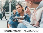 two young women outdoors eating ... | Shutterstock . vector #769850917