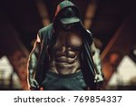 Small photo of Young strong man bodybuilder with informal style clothing with hood standing in urban city interior. Dark red colors.