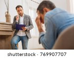 Small photo of Solving trouble. Handsome thoughtful male psychologist holding blue folder and looking at patient while he crying