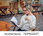 beautiful young woman reading a ... | Shutterstock . vector #769962037