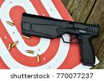 Small photo of firearm sound suppressor on the target and wooden background