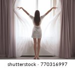 young woman opening curtains at ... | Shutterstock . vector #770316997