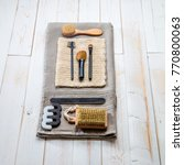 Small photo of Design display of female body care and beauty accessories for eco-friendly face and body brushes, nailcare and makeup products over natural white wooden background, top view