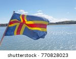 Small photo of Flag from Aland (autonomous province of Finland), archipelago in the background