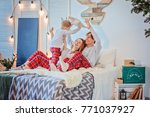 Small photo of Family have fun and laughs on the bed / Parents play with their child and laugh / place under the text