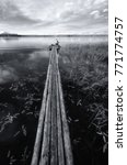 Small photo of A long decking of logs goes far into the lake. At the far edge of the deck, a man sits and catches fish. Black and white. Background. Vertical.