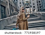 Small photo of Always confident in her style. Attractive young woman drinking coffee while walking up the steps outdoors