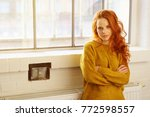 Small photo of Serious intense young redhead woman sitting on a radiator with folded arms staring at the camera with copy space alongside