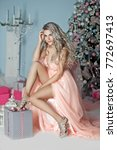 Stock photo woman in pink dress with christmas box gift near pink white christmas tree 772697413