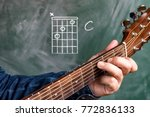 Small photo of Man in a blue denim shirt playing guitar chords displayed on a blackboard, Chord C