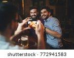 men drink beer in a pub. | Shutterstock . vector #772941583
