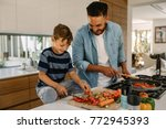 little boy cutting vegetables... | Shutterstock . vector #772945393