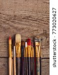 Small photo of Row of artist paintbrushes closeup on retro wooden table.