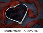 Small photo of Heart shaped small slate blackboard on slate background. Silky and sheer red ribbon winding around. Valentine message added. Vignette added.