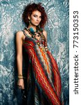 Small photo of Beautiful bright woman with curly foxy hair wears a dress and beads in boho style. Ethnic style in clothes.
