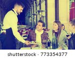 smiling waiter serving guests... | Shutterstock . vector #773354377