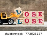 Small photo of Yellow toy bulldozer hold letter block L to complete word lose lose on wood background