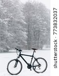 Small photo of Winter season cycling. Black bicycle on the snow. Sport at any time of year concept.