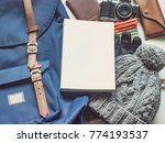 Small photo of long holiday travel flat lay concept from winter cloth item and blue backpack with passport , retro camera , sunglasses and book put on isolated white background